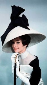 1963: Actress Audrey Hepburn wearing costume with wide lampshade hat topped with bow and holding walking stick, all designed by Cecil Beaton for the Broadway musical 'My Fair Lady'. (Photo by Cecil Beaton)