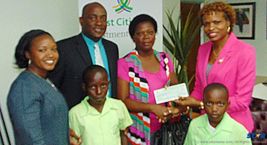 From L-R (rear): First Citizens Marketing Officer Nicole McDonald, Minister for Youth and Dennery North MP Shawn Edward, Principal of the Richfond Combined Sonjane Marcelle-Etienne, First Citizens Regional Manager Carole Eleuthere-Jn Marie and, upfront, students of the Richfond Primary.