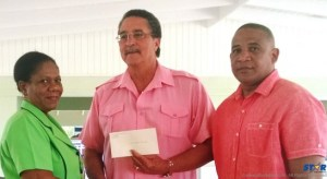 Comfort Bay Manager Mrs. Gertrude Gustave receives cheque from PM Anthony as St Lucia's High Commissioner to the UK, Ernest Hilaire looks on.