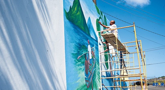 One of the artists is seen here painting the mural on the 100 foot wall near     Faux-a-Chaud in Castries. (Photo Bill Mortley).