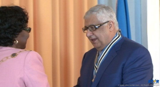 Proud Saint Lucian (at heart!) Gilbert Chagoury at the  moment he received from Governor General Pearlette Louisy the nation's highest  honor—The Saint Lucia Cross.