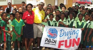 Sandals Foundation representatives Terrol and Orena embrace the students of the Gros Islet Primary School following the outdoor 'World Oceans Day' exercise on school grounds.