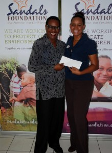 MD of the Crisis Center Norma Laborde (left) receives cheque from Sandals PR Manager Rhonda Giraudy