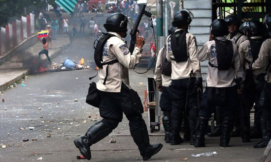 Riot police clash with residents of La Vega, a low-income neighborhood in Caracas, Venezuela earlier this month. Photograph: AFP/Getty Images