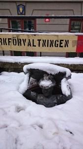 Памятник дорожному рабочему в сугробе снега