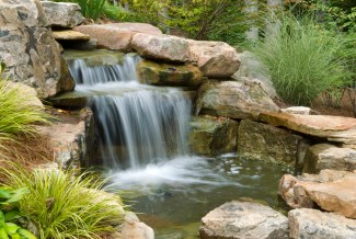 Long exposure of a backyard waterfall and pond surrounded by green foliage.