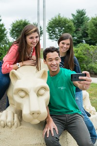Three students at Penn State Harrisburg take a selfie with the Nittany Lion Shrine.