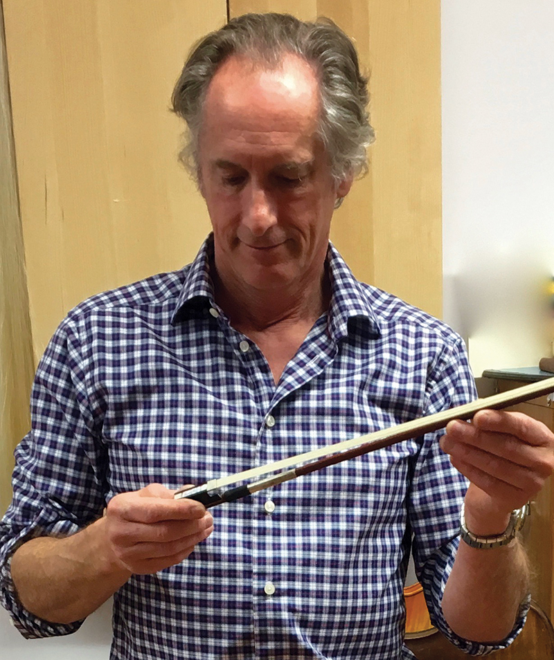 Violin maker, appraiser, and dealer David Bonsey examines a bow by Josephine Thomachot