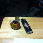 smoke trailing off a glass marijuana pipe near a lighter