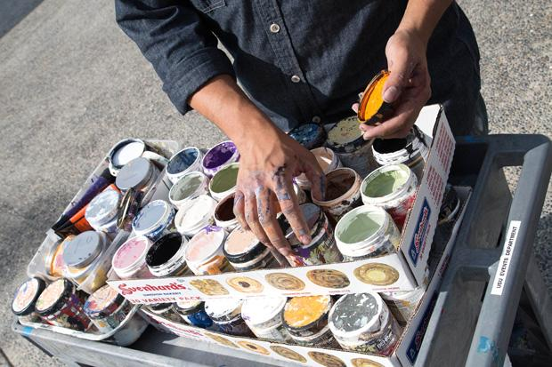 Guest artist, Ronnie Robles, prepares his paint at the Art 180 event held at the USU on Thursday. Passersby were encouraged to paint over his work as well as draw and paint old records for display. Clotheslines in the back of the stage were used as impromptu easels for the various works produced. Photo credit: Nathan McMahon / Opinion Editor