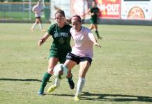CSUN soccer player (pink) attempts to steal ball away from opponent (green))