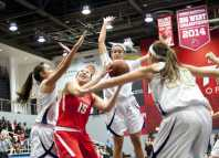 CSUN basketball player struggles to fight through three Master's College Women basketball players.