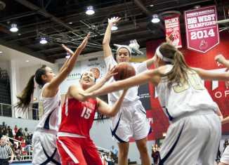 CSUN basketball player struggles to fight through three Master's College Women basketball players.