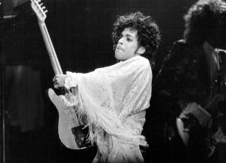 Prince playing guitar on stage