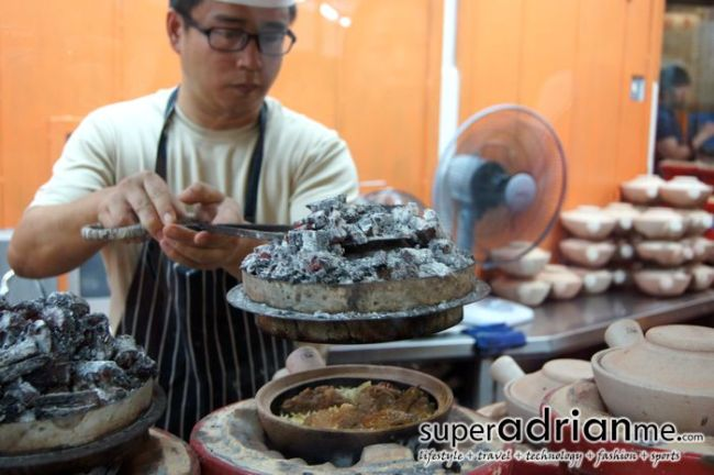 Placing burning charcoal on top of the claypot
