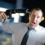 Man holding petrol pump nozzle to his head