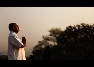 Man standing with eyes closed & hands held in prayer at dawn
