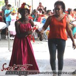 Girl in red dress with flowered bonnet held by woman in orange top and black leggings at special needs children Easter Bonnet parade at Queen's Park Cricket Club, color eggs, Sweet T&T, Sweet TnT, Trinidad and Tobago, Trini, vacation, travel
