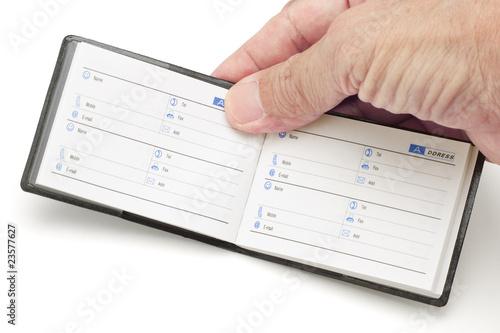 Hand holding mini address book\