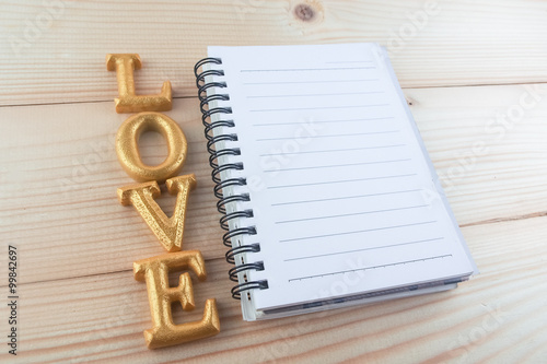 wood letter word love with notebook on wood background\