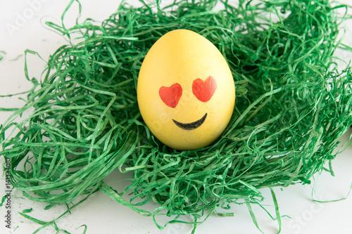 Happy easter emoji as easter egg in green gras - heart shaped eye