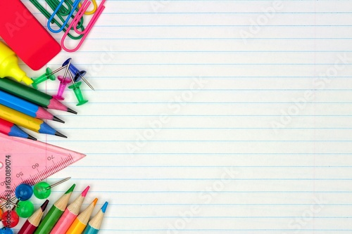 Colorful school supplies side border over a lined paper background - line paper background