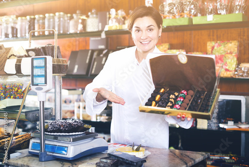 Shop assistant demonstrating box of chocolates\