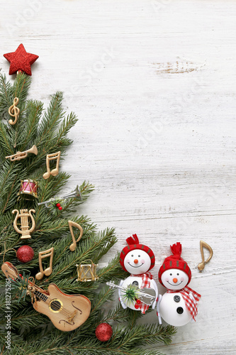 Snowman with christmas tree , music notes, instruments on wooden