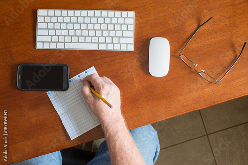 person writing in check ledger register online banking desk keyboard