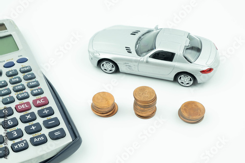 Miniature car model, coin and calculator on white background, Buying