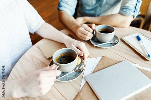 Hands of unrecognizable man and woman having coffee during business