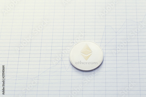 Price of Ethereum coin concept with silver coin laid on chart