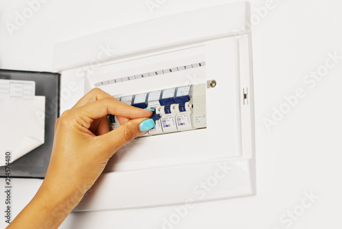 Woman\u0027s hand turning off electrical fuse box \