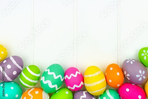 Colorful Easter egg bottom border against a white wood background