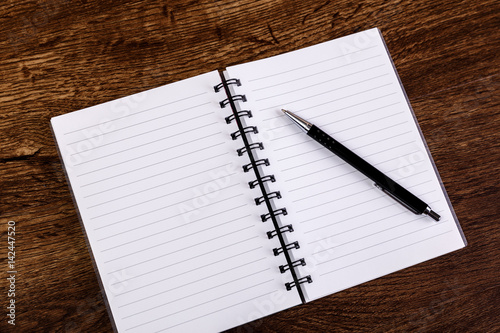 Notepad with pen on the wooden rustic desk Mockup concept with - blank diary page