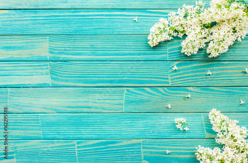 Flowers background Lilac flowers on turquoise wooden background