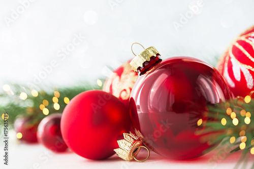 Red christmas ornaments on glitter holiday background with xmas tree - christmas theme background