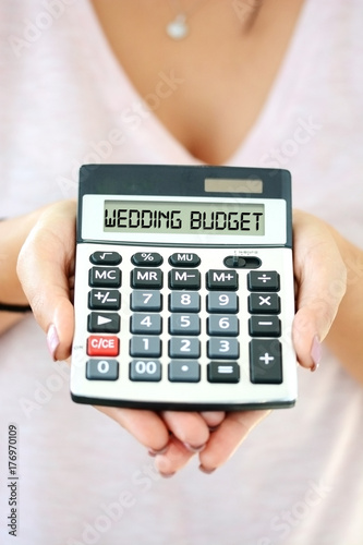 Wedding cost concept with small calculator in woman hand spelling