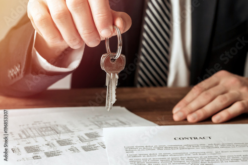 Real estate agent giving house key to his client after signing