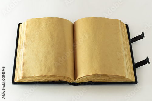 Opened book with aged yellow page, clasps and wavy paper edges - opened book