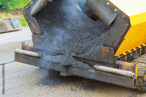 Close view on the workers and the asphalting machines asphalt with - asphalting machine