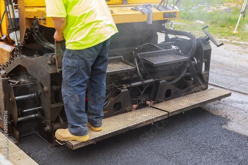 Worker on Asphalting paver machine during Road street repairing