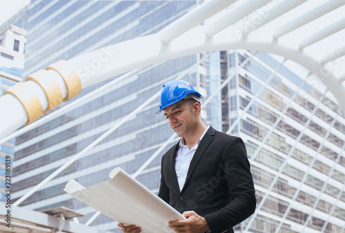 Male construction engineer holding a blueprints reading details of