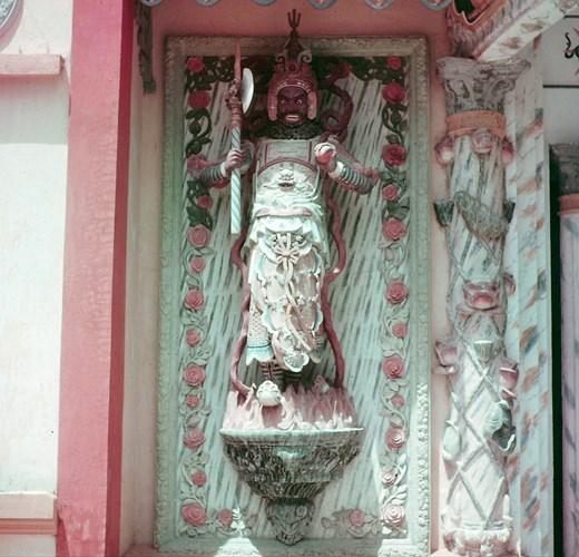 Phía bên trái là tượng ông Ác, cũng mặc khôi giáp, nhưng gương mặt dữ dằn, một tay cầm búa, một tay cầm Ngọc ấn tỷ phù, tượng trưng cho điều Ác (vọng tâm).