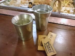 錫の上燗コップ、タンポの燗酒と勘定用の酒札(木札)