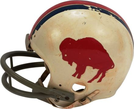 "1972 Dick Cunningham Buffalo Bills Game Worn Helmet This fantastic Buffalo Bills helmet was game worn by Dick Cunningham in 1972 and features the rare, standing buffalo style only used until 1973. The red standing buffalo stickers appear on both sides of the helmet, with red and blue stripes on top. The Riddell helmet has original ""water pack"" padding inside. The number ""63"" is written in marker inside the right ear piece, which was the number worn by Cunningham in '72. The helmet shows nice use with scuffs and bruises, and some of one of the blue stripes on top is chipped. There is a May 1972 manufacturer's sticker inside underneath the padding. Sold for: $1,250.40"