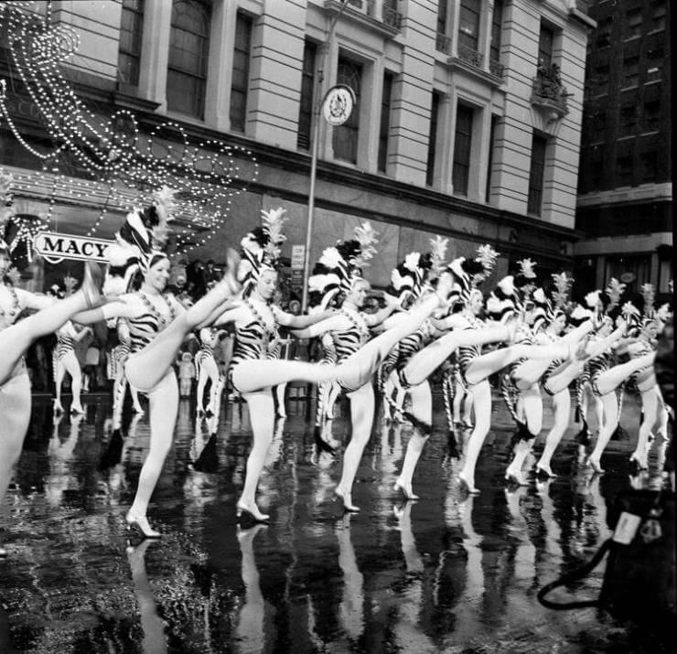 Members of the Radio City Music Hall Rockettes entertain crowds in front of rain-streaked Macy's department store, Nov. 25, 1971. The Rockettes were one of the many attractions of the 44th annual Macy's Thanksgiving Day Parade. (AP Photo/Ed Ford)