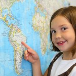 Elementary students points to location on a world map
