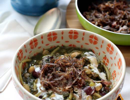 Persian noodle soup topped with yoghurt and fried onion and mint.
