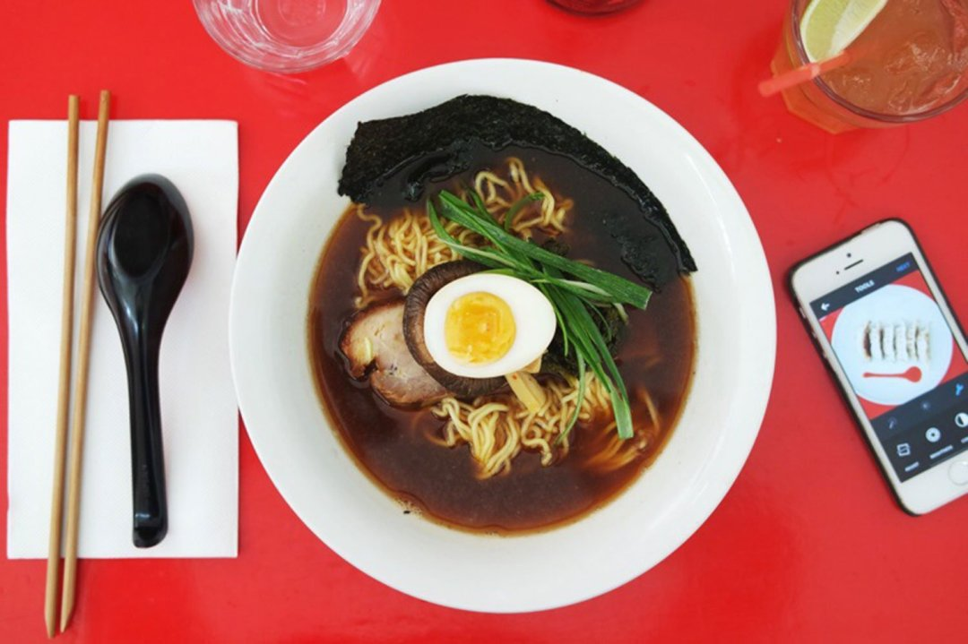 "A bowl of ""the darkness"" ramen from Rising sun workshop, photographed aerially with cutlery and a mobile phone flanking it from either side."